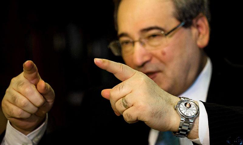 """نائب وزير الخارجية، فيصل المقداد يرتدي ساعة تحمل صورة الأسد خلال مقابلة مع وكالة """"أسوشييتد برس"""" - 13 نيسان 2016"""