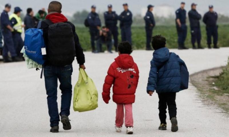 """اللاجئون أثناء مغادرتهم مخيم """"إيدوميني"""" في اليونان - الثلاثاء أيار (AFP)"""