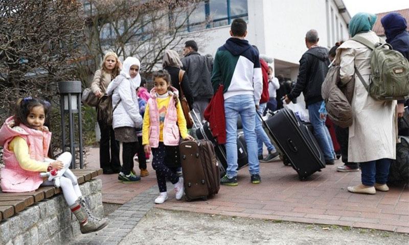 لاجئون سوريون أمام أحد مخيمات اللجوء في ألمانيا (رويترز)