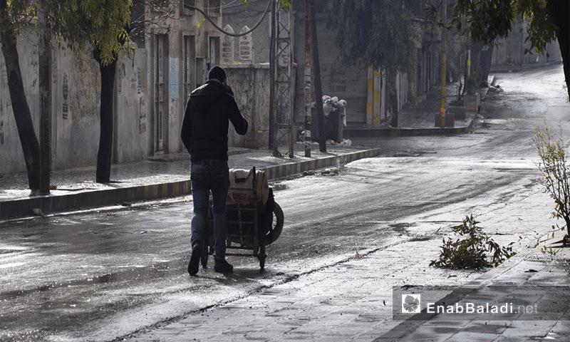 شاب يدفع حقائبه في حي من أحياء حلب المحاصرة - 2 كانون الأول 2016 - (عنب بلدي)