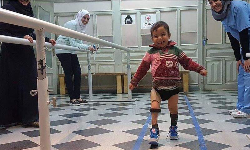 طفل سوري فرح بقدمه الجديده بعد أن فقد السابقة بسبب القصف_(تويتر)
