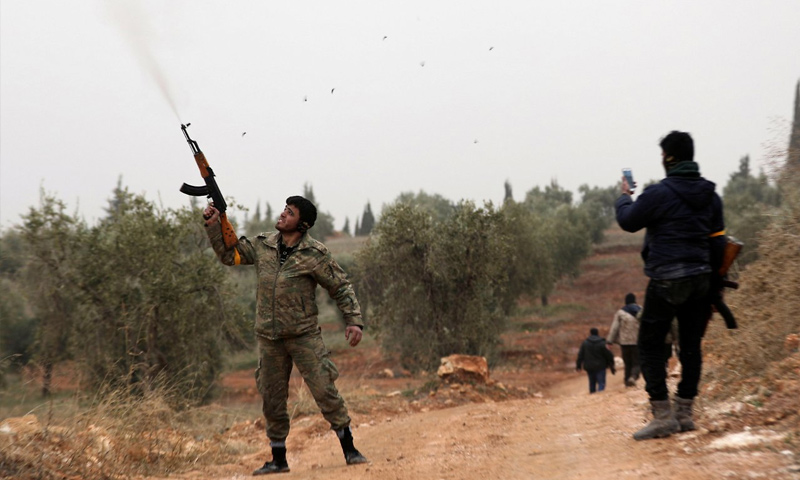 عنصر في الجيش الحر يطلق الرصاص فرحًا بالسيطرة على جبل باريسا في محيط عفرين - كانون الثاني 2018 (رويترز)