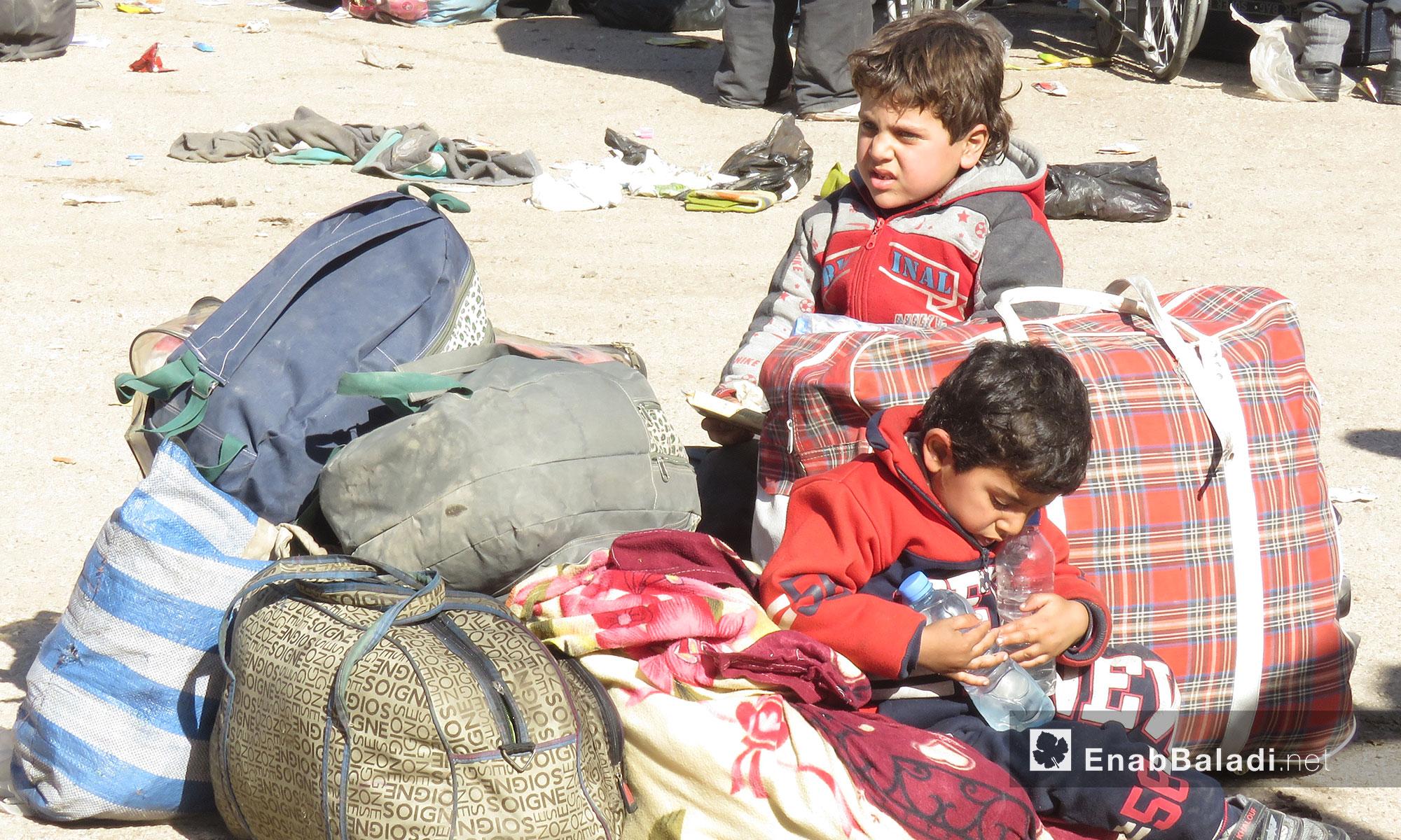 طفلان من مهجرو عربين لحظة وصولهم إلى قلعة المضيق بريف حماة - 26 آذار 2018 (عنب بلدي)