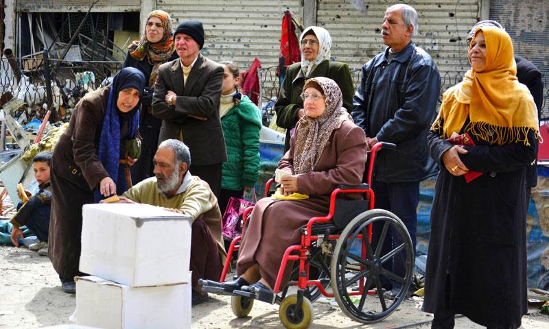 مواطنون ينتظرون المساعدات الإنسانية في مخيم اليرموك بدمشق - 15 نيسان 2015 (رويترز)
