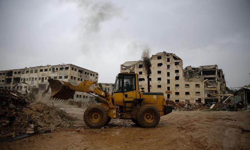 جرافة تزيل الركام من أضرار الحرب في حي الليرمون بحلب (AP)