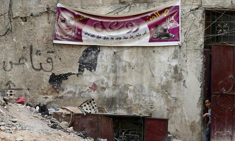 طفلة تخرج من باب بجانب إعلان لصالون حلاقة في حي القابون بدمشق - 14 آذار 2016 (رويترز)