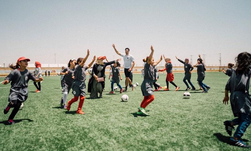 أطفال مخيم الزعتري مع لاعب كرة القدم الأمريكي جورج جون (Kickstart joy)