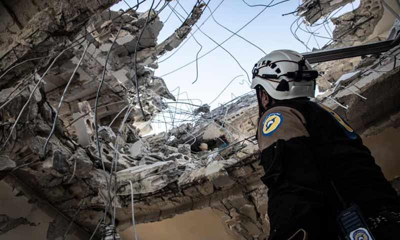 عنصر من الدفاع المدني ينظر إلى السماء من فتحة سقف منزل مهدم - 30 من كانون الأول 2019 (الدفاع المدني في حلب)