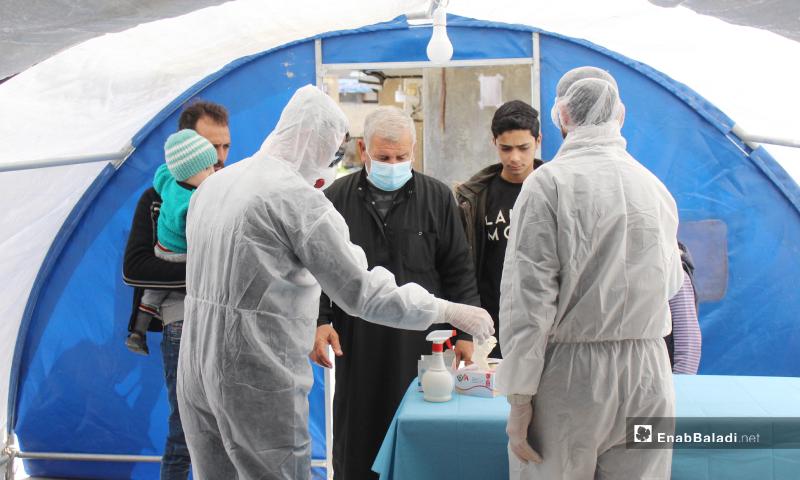 مرضى يوجه لهم تعليمات للوقاية من فيروس كورونا ضمن المشفى وفرزهم حسب الحالة المرضية في القسم المستحدث بمشفى كفرتخاريم للوقاية من كورونا - 27 آذار 2020 (عنب بلدي)