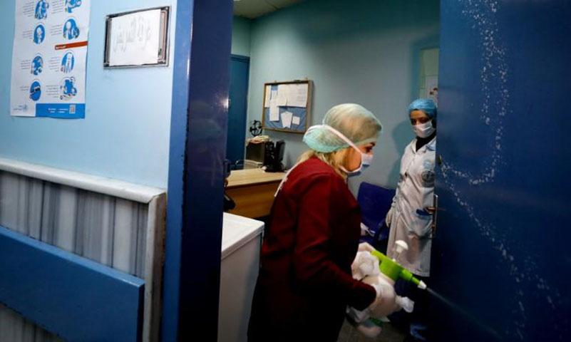امرأة من العاملين بالرعاية الصحية تقوم بتعقيم باب في مستشفى بدمشق(رويترز)
