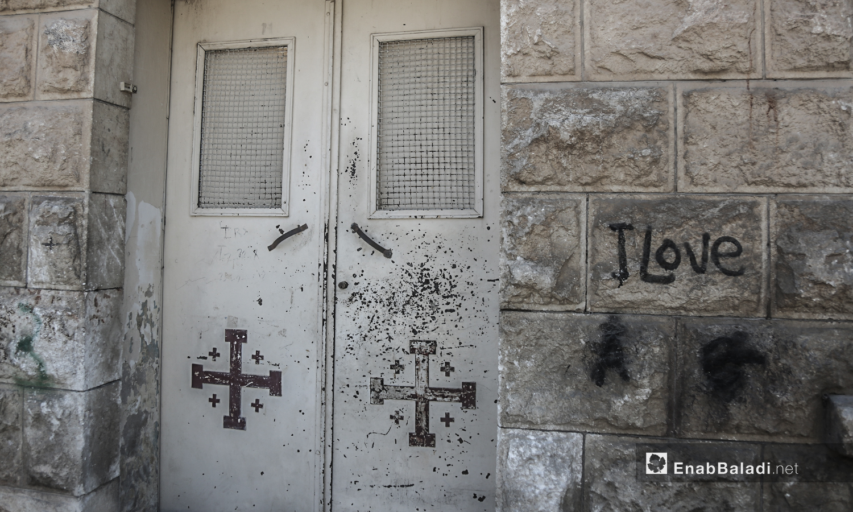 """باب حديدي لكنيسة """"مار يوسف"""" تظهر عليه علامات الصدأ فوق الصلبان المرسومة على واجهته - تموز 2020 (عنب بلدي)"""