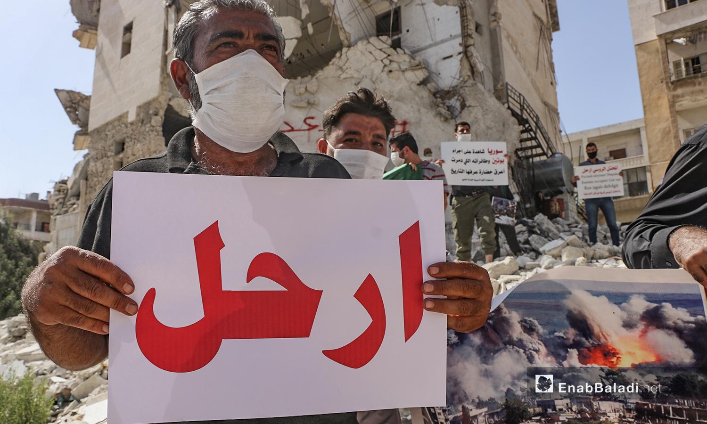 رجل يحمل لوحة كتب عليها: ارحل في الذكرى الخامسة للتدخل الروسي في سوريا في مدينة إدلب - 30 أيلول 2020 (عنب بلدي /أنس الخولي)