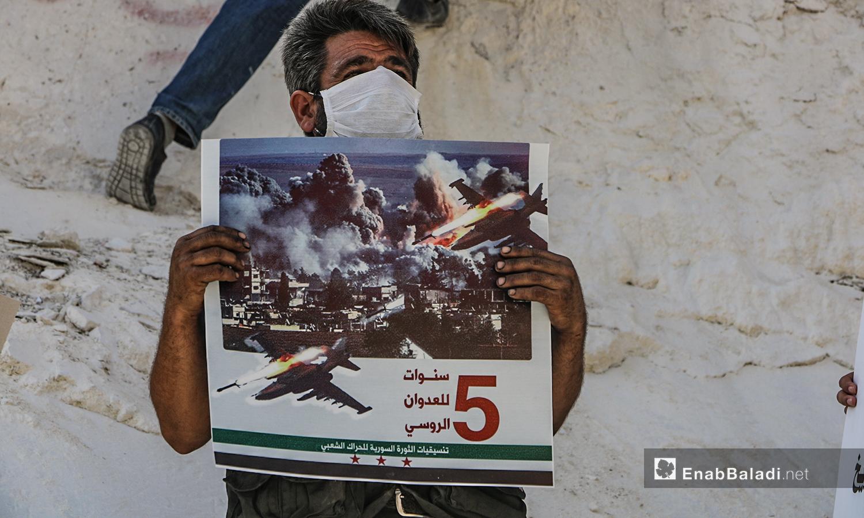 ناشط  في إدلب يحمل لافتة تستنكر الانتهاكات الروسية في سوريا خلال خمس أعوام من التدخل العسكري - 30 أيلول 2020 (عنب بلدي/أنس الخولي)