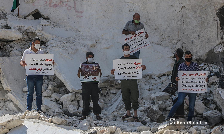 ناشطون في إدلب يحملون لافتات تستنكر الانتهاكات الروسية في سوريا خلال خمس أعوام من التدخل العسكري - 30 أيلول 2020 (عنب بلدي/أنس الخولي)