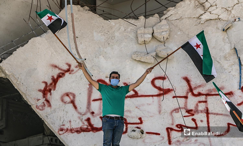 ناشط يحمل علم الثورة خلال وقفة احتجاجية تطالب بمغادرة روسيا لسوريا - 30 أيلول 2020 (عنب بلدي/ أنس الخولي)