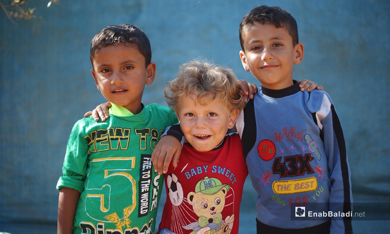 """ينظر الأطفال في مخيم """"المطار"""" مبتسمين إلى الكاميرات التي أتت لرصد حياتهم في المخيم الأخضر  - تشرين الأول 2020 (عنب بلدي/ يوسف غريبي)"""