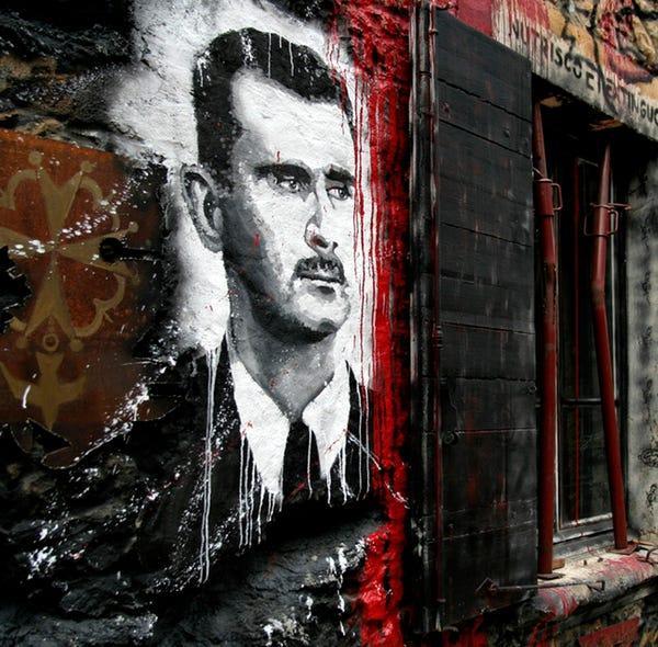صورة لرئيس النظام السوري على جدار في سوريا- (Thierry Ehrmann)