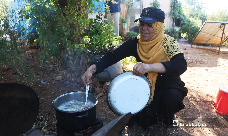 تطهو حورية طعام عائلتها بين النباتات المحيطة بخيمتها  - تشرين الأول 2020 (عنب بلدي/ يوسف غريبي)