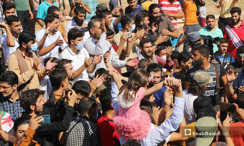 رجل يحمل ابنته على أكتافه خلال مظاهرة تندد بالتواجد الروسي في سوريا - 2 تشرين الأول 2020 (عنب بلدي/ أنس الخولي)