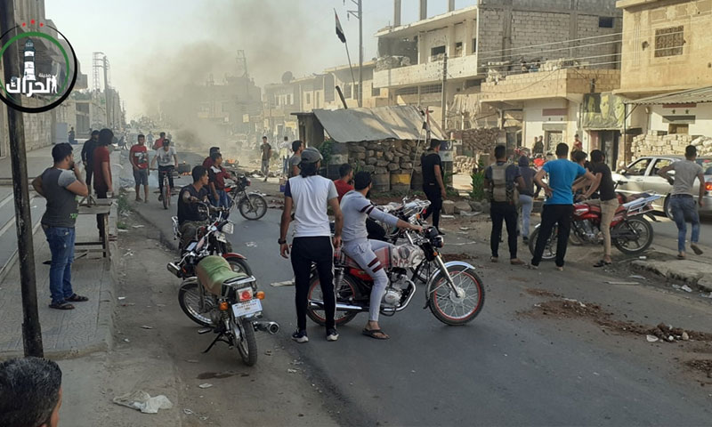 صورة من تجمع مواطنين عند الحاجز الأمني الذي حرق في مدينة درعا 26 من تشرين الأول 2020 (صفحة الحراك في فيس بوك)