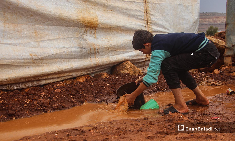 طفل يبعد المياه من بين الخيم بعد هطول الأمطار في مخيم الرمضون على أطراف قرية كفر عروق شمالي إدلب - 2 تشرين الثاني 2020 (عنب بلدي/إياد عبد الجواد)