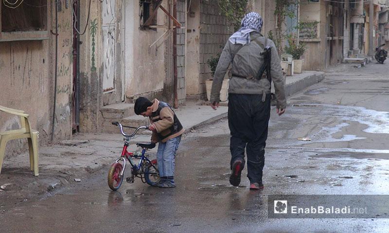 A child with a fighter in al-Sheikh Yassin neighborhood, Deir ez-Zor - 2013 (Enab Baladi archive)