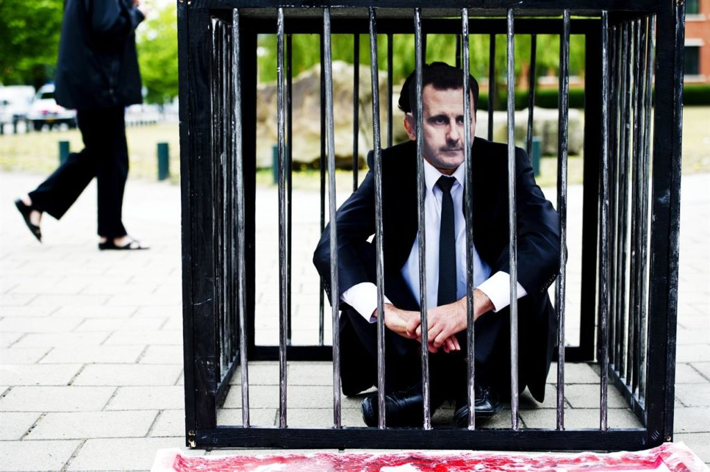 A protester wearing a mask of the President of the Syrian regime, Bashar al-Assad, sits on the ground inside the dock in front of the International Criminal Court in The Hague, western Netherlands - June 7, 2011 (ROBIN UTRECHT / ANP / AFP)