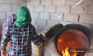 Women baking flatbreads in a tandoor oven  in the village of killi in the northern countryside of Idlib - October 2020 ((Enab Baladi / Iyad Abdel Jawad) )